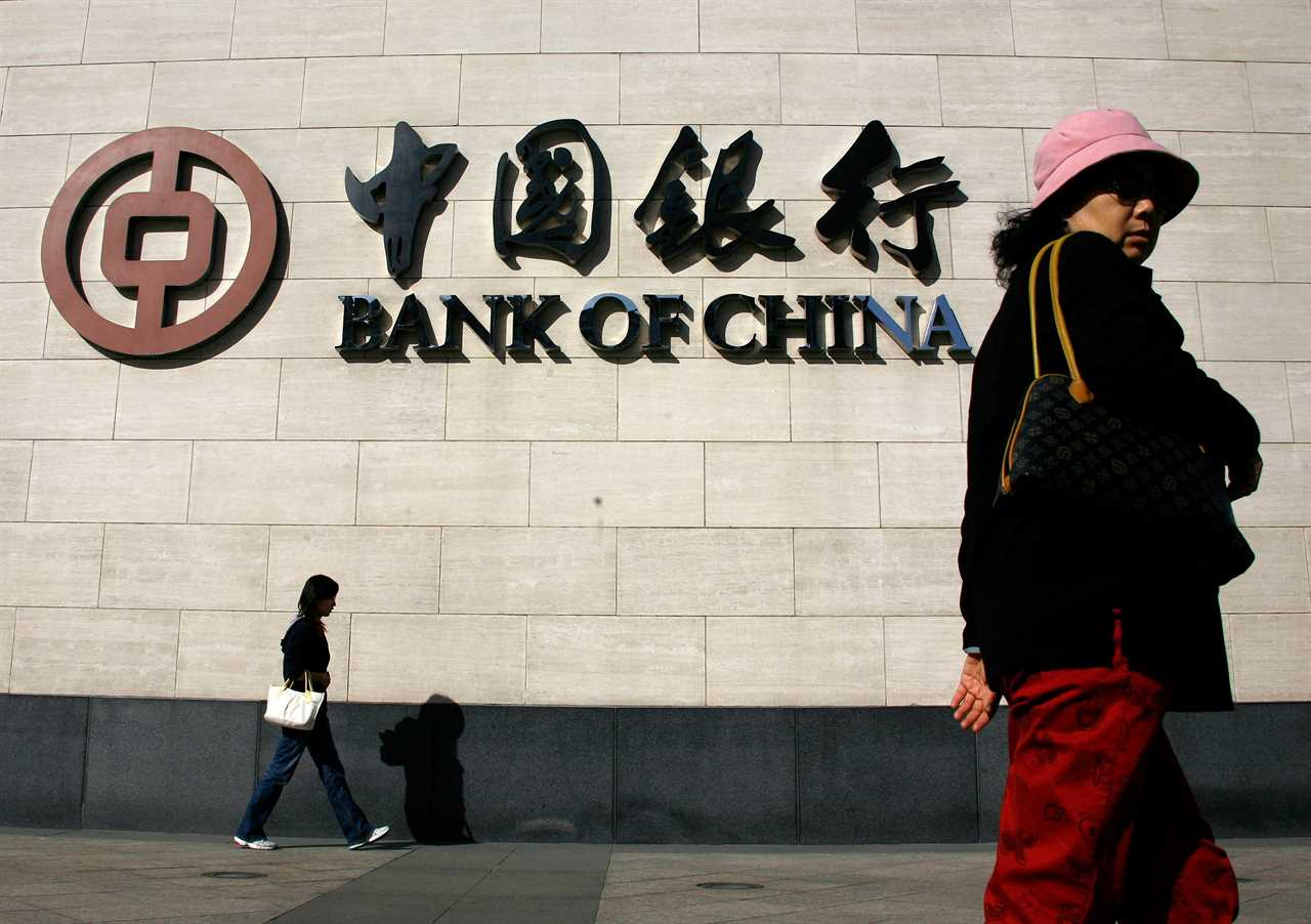 FILE PHOTO: People walk past the China Bank headquarters building in central Beijing October 15, 2008.  REUTERS/David Gray (CHINA)