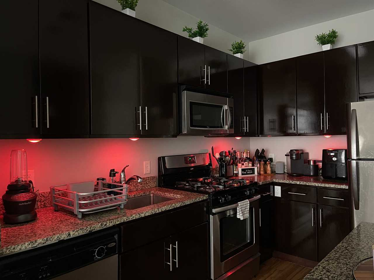 Red LED lights under cabinets illuminating the kitchen counter